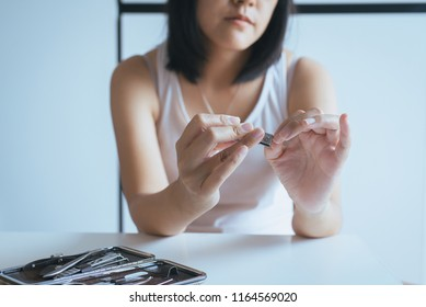 Woman cutting nails with nail clipper,Female using tweezers clipping hes fingernails
