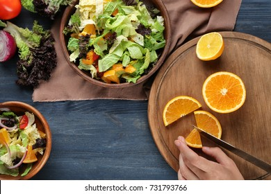Woman cutting orange for kale salad on table