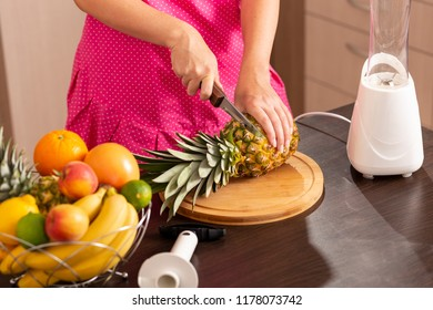 Woman cutting a pineapple top with a kitchen knife on a cutting board in order to peel it with a pineapple cutter