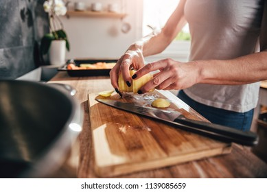 Woman cutting potato on cutting board