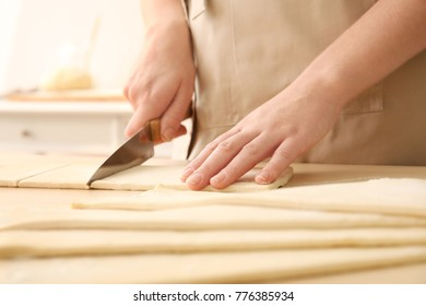 Woman cutting puff pastry on table
