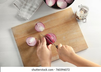Woman cutting red onion on wooden board