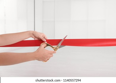 Woman cutting red ribbon on blurred background. Festive ceremony