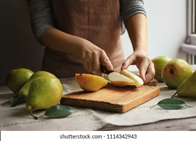 Woman cutting ripe pears on table