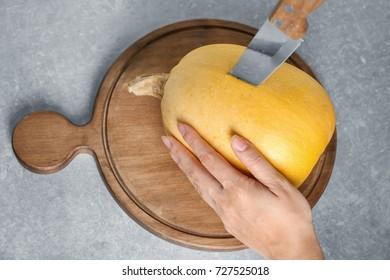 Woman cutting ripe spaghetti squash on wooden board