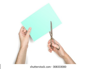 A woman is cutting a sheet of green paper using  metallic scissors, isolated on white background