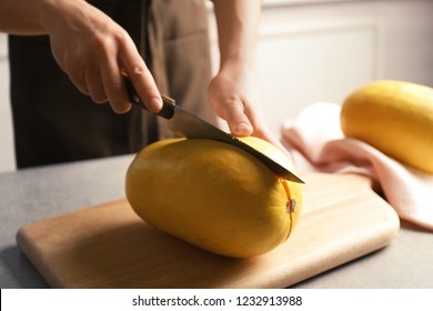 Woman cutting spaghetti squash on table in kitchen, closeup