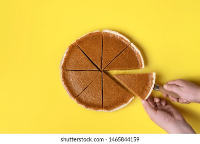 Woman cutting and taking a slice of pumpkin pie on a yellow paper background. Flat lay of traditional American pie. Thanksgiving sweet pastry item.