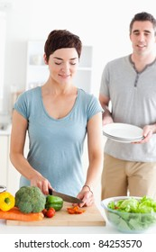 Woman cutting vegetables and man holding plates in a kitchen