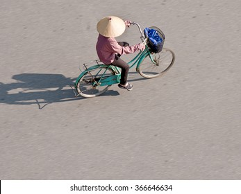 A woman cycles on her bicycle in Vietnam, motion blur