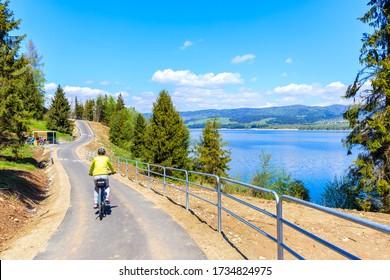 Montañas Pieniny Mountains, Polonia, en bicicleta por el lago Czorsztynskie cerca de la aldea de Niedzica el día soleado de primavera