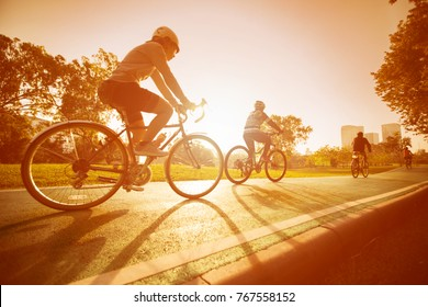 A woman is cycling into the sunset in the park.