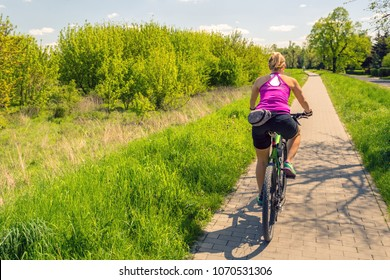 Woman cycling a mountain bike in a city park, summer day. Inspire and motivate concept for outdoors activity. Girl cyclist riding bicycle on a paved road.