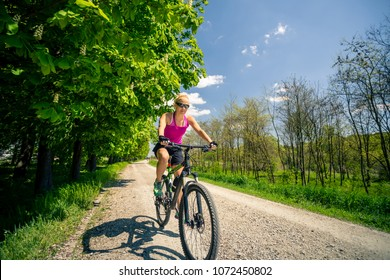 Woman cycling a mountain bike in a city park, summer day. Inspire and motivate concept for outdoors activity. Girl cyclist smiling and riding bicycle on a dirt road.