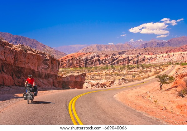Woman cycling on the empty road to Cafayate in the remote part of north west Argentina