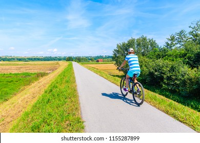 Woman cycling on path along green fields and Vistula river near Cracow city on sunny summer day, Poland