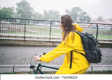 Woman cycling in the raincoat. Biking in the rain