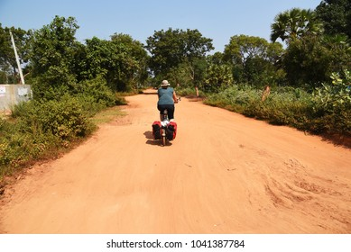 Woman cycling through the Wilpattu National Park,Sri Lanka