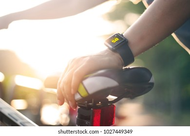 woman cyclist hand with smart watch on saddle bicycle at summer trail.