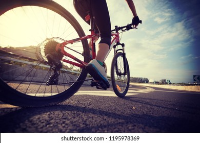 Woman cyclist legs riding Mountain Bike on highway