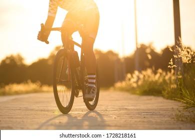 Woman cyclist legs riding Mountain Bike on highway sun set , hi key