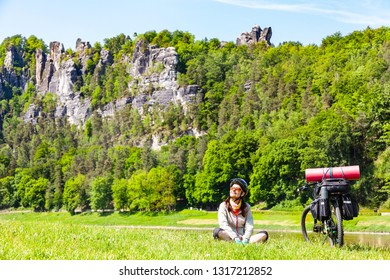 Woman cyclist with loaded bicycle having break while travelling. Germany, Saxon Switzerland.