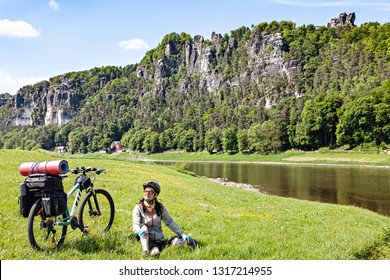 Woman cyclist with loaded bicycle having break while travelling. Germany, Saxon Switzerland