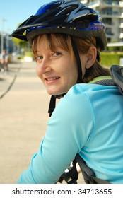 Woman cyclist looks back while cycling along a bike path.