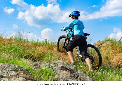 Woman cyclist pushing her bike up a steep slope.