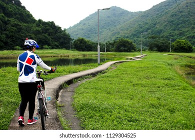 The woman cyclist pushing her mountain bike on narrow track during the bicycle adventure travel  in Hong Kong on 20 Sept 2017