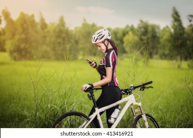 Woman cyclist relaxing and using smartphone