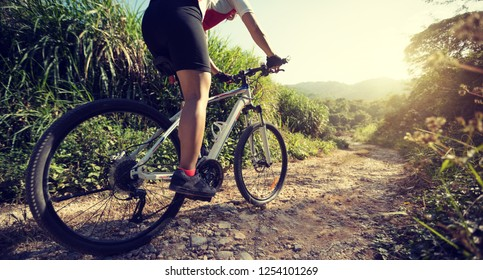 Woman cyclist riding a bike on a nature trail in the mountains.people living a healthy lifestyle