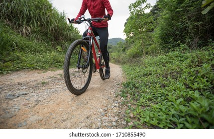 Woman cyclist riding a bike on a nature trail in the mountains