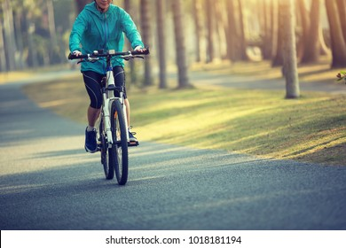 Woman cyclist riding bike with outstretched arms in tropical park
