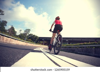 Woman cyclist riding Mountain Bike on highway