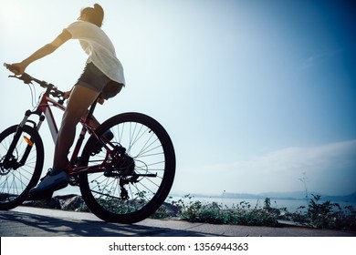 Woman cyclist riding Mountain Bike on sunrise seaside