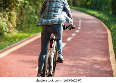 Woman cyclist riding mountain bike in park