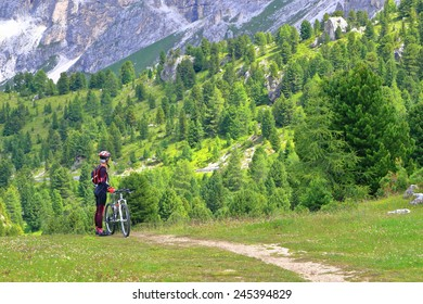 Woman cyclist standing along narrow trail with distant forest in the background, Dolomites Alps, Italy