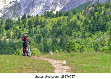 Woman cyclist standing near mountain bike in the area of Sella pass, Dolomites Alps, Italy