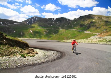 Woman cyclist training on a mountain road