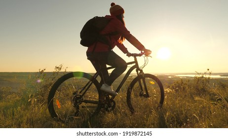 Woman of a cyclist traveler rides along the edge of the mountain, admiring the landscape and the sunrise. Free tourist rides a bike in nature in the sun. Sports lifestyle. Cyclist exercising