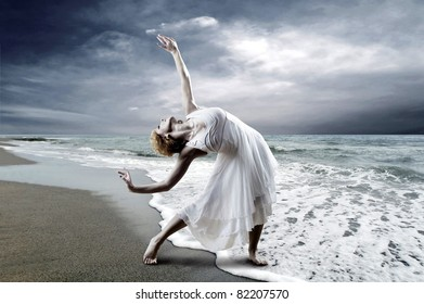 Woman dancer posing on the beach