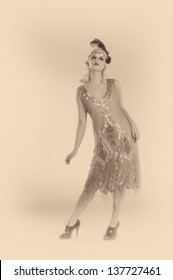 Woman dancing in a 1920's beaded flapper dress in sepia toned black and white.