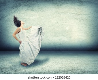 a woman dancing in an empty room made of concrete