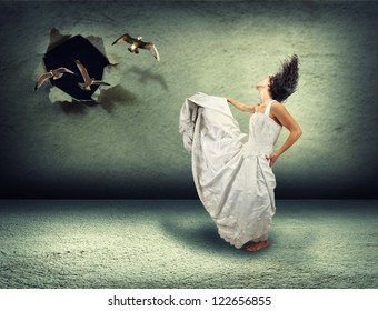 a woman dancing in an empty room made of concrete with a hole in the wall where birds are flying out