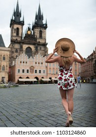 Woman dancing in a flower dress at old town square in prague, czech replic