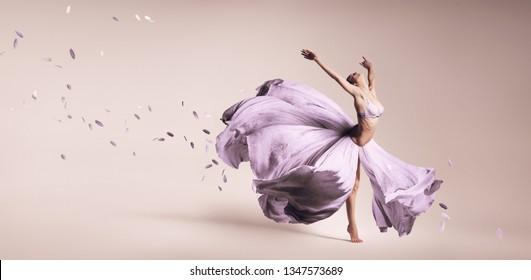 Frau tanzt in fließendem violettem Kleid im Studioaufnahme