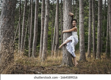 A woman dancing gracefully in the open air beside a tree in the forest. Woodstock, New York State, USA