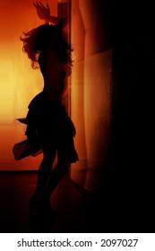 Woman dancing samba in dark red room