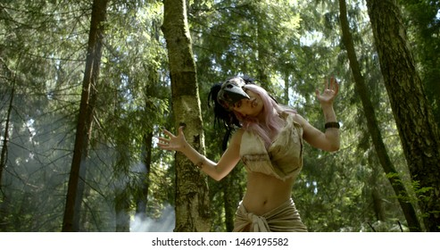 woman is dancing shamanic ritual dance in forest between tall pines